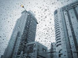 Raindrops on car glass at city in rainy day photo