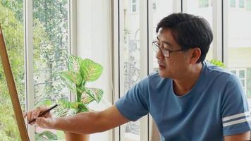 Anciano asiático sentado felizmente con dibujo en casa concepto de vivir una vida feliz después de la jubilación video