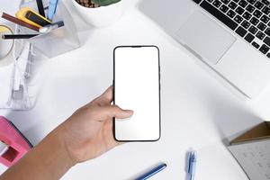 Man using a smartphone blank screen mock up at the white office desk photo