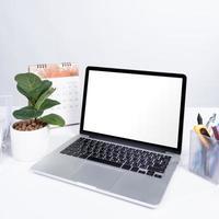maqueta de pantalla en blanco portátil en el escritorio de oficina blanco foto