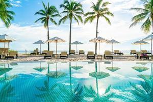 Beautiful umbrella and chair around swimming pool in hotel and resort photo