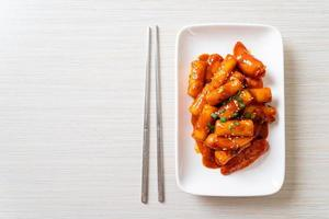 Korean rice cake stick with sausage in spicy sauce photo