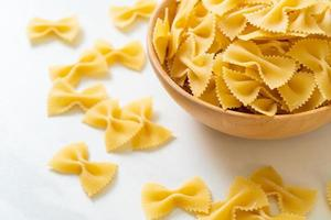 Dry uncooked farfalle pasta in bowl photo