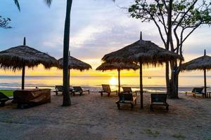Umbrella and chair on tropical beach with sunrise photo