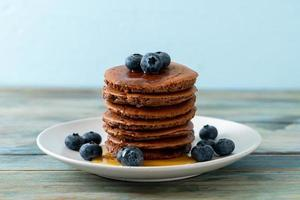 Chocolate pancake stack with blueberry and honey on a plate photo