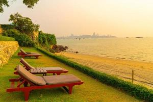 Beach chairs with a beach sea background at sunset time in Pattaya, Thailand photo