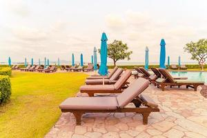 Beach chairs and swimming pool with a beach sea background at sunset time in Pattaya, Thailand photo