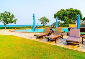 Chair pool or bed pool and umbrella around swimming pool with sea background photo