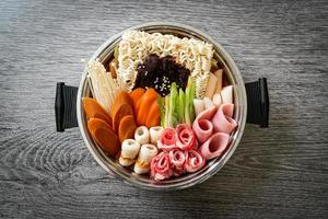 Budae Jjigae or Budaejjigae, Army stew or Army base stew, with kimchi, spam, sausages, ramen noodles, and more - popular Korean hot pot food style photo