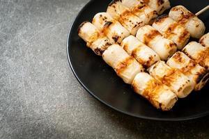 Pastel de pasta de pescado en forma de tubo a la parrilla o pincho de calamar en un plato foto