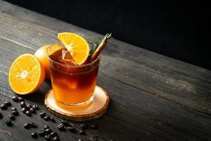 A glass of iced Americano black coffee and a layer of orange and lemon juice decorated with rosemary and cinnamon photo