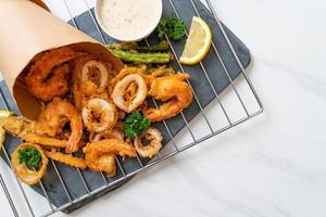 mariscos, camarones y calamares fritos, con mezcla de vegetales - estilo de comida poco saludable foto
