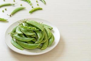 Guisantes verdes dulces frescos en una placa blanca. foto