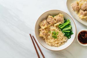fideos de huevo secos con wonton de cerdo o albóndigas de cerdo sin sopa - estilo de comida asiática foto