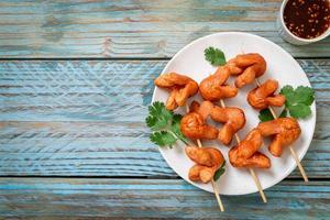 Deep fried sausage skewer with dipping sauce photo