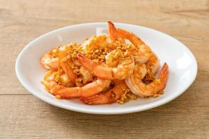 Fried shrimp or prawns with garlic on a white plate - seafood style photo
