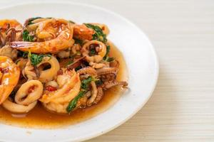 Rice and stir-fried seafood, shrimp and squid, with Thai basil - Asian food style photo
