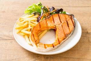 Grilled salmon steak fillet with vegetables and french fries on a plate photo