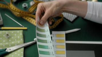 Costurera de mesa diseñando ropa, vista lateral sobre fondo verde video