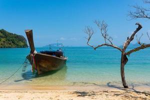 bote de cola larga en el mar azul en verano foto