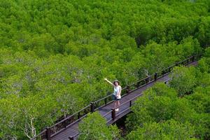 Vista desde arriba de la joven mujer asiática caminando por un sendero de madera en el bosque de manglares durante las vacaciones de verano foto