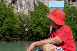 Senior asian man travel on long tail boat to see mangrove forest on summer vacation photo