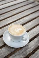 Cappuccino cup on wood background photo