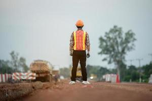 Construction engineer supervising work at construction site photo