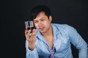 Handsome handsome man drinking whisky at home photo