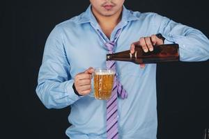 Cropped close up of a man drinking beer at the home photo