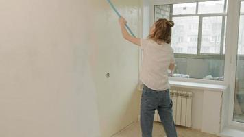 A Woman Paints a Wall Beige with A Roller video
