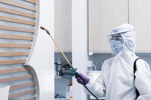 trabajador con equipo de protección personal que incluye máscara de traje blanco y protector facial con desinfectante para controlar la infección por coronavirus en la clínica del dentista foto
