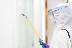 trabajador con equipo de protección personal que incluye máscara de traje blanco y protector facial con desinfectante para controlar la infección por coronavirus foto
