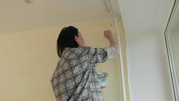 Young Person Paints the Top Corner of the Wall video