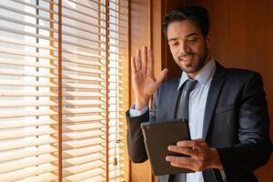 Joven empresario de Oriente Medio empresario con tableta para hablar con el cliente a través de la aplicación de videollamada en la oficina foto