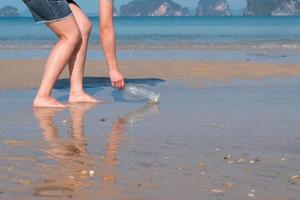 Joven asiática recogiendo botellas de plástico usadas de la playa para salvar el medio ambiente y el ecosistema marino foto