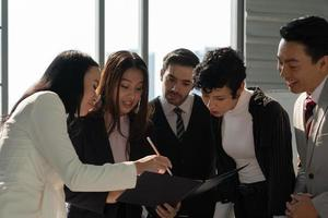 International business team including caucasian and asian people standing near window in office and discussing about project photo