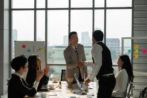 Middle age asian executive manager handshaking with client in meeting photo