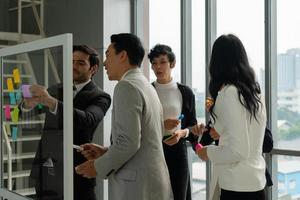 Multiethnic business team including caucasian and asian people working together in office photo