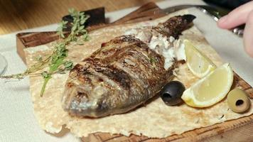 Cerrar tiro dolor de pescado a la parrilla con aceitunas y una rodaja de limón en pan de pita video