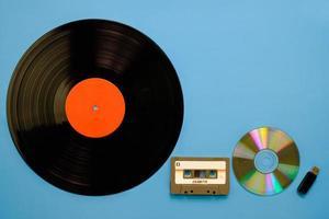 Una colección de equipos musicales retro antiguos y modernos, tecnología de grabación de gramófono, cinta de casete de audio, disco compacto y unidad flash sobre fondo azul. foto