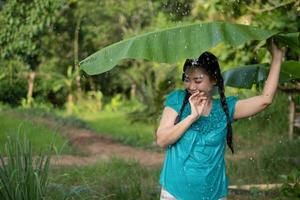 Blurred image portrait of a young Asia woman with black hair holding a banana leaf in the raining at the green garden background photo