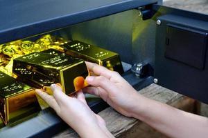 Caja de seguridad de acero electrónica abierta de mano llena de pila de monedas y ba de oro foto