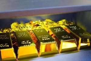 Caja fuerte de acero llena de monedas y pila de barras de oro. foto