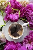flores de peonía rosa y taza de café foto