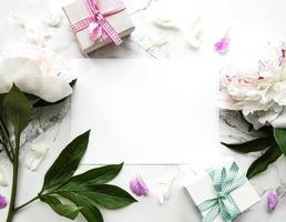 Peonías rosas con tarjeta vacía y caja de regalo sobre fondo blanco. foto