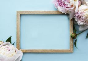 Wooden frame surrounded by beautiful pink peonies on a blue background photo