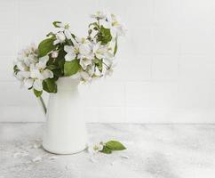 flor de manzana de primavera en un jarrón blanco foto