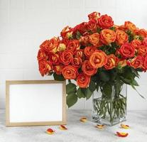 Red roses in a glass vase with an empty photo frame