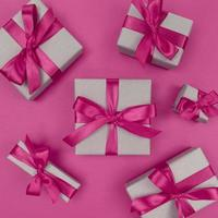 Gift boxes wrapped in craft paper with pink ribbons and bows Festive monochrome flat lay photo